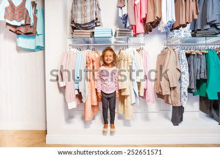 Smiling girl standing between clothes on hanger