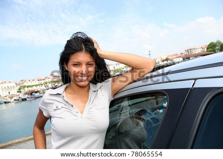 Smiling girl standing by car in tourist town - stock photo