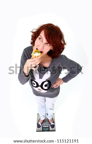 Smiling girl standing on the scales and eating cake isolated on white background - stock photo