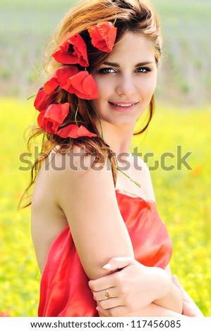 smiling girl standing with poppies in her hair - stock photo