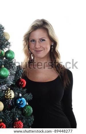 Smiling Girl stands next to christmas tree - stock photo