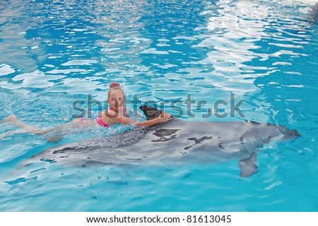 Smiling Girl Swimming with the Dolphin in the Swimming Pool