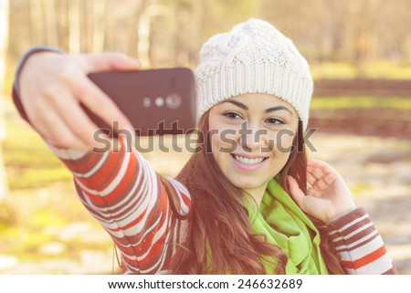 Smiling girl taking selfie with phone outdoor. - stock photo