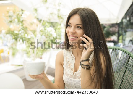 Smiling girl talking on the phone and drinking coffee.