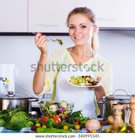 Smiling girl tasting vegetable salad she cooked at home