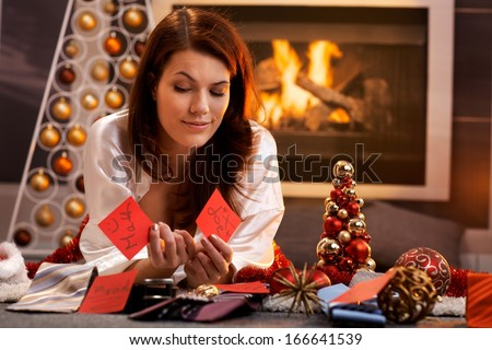 Smiling girl thinking to decide on christmas presents, arranging name tag with tie, lying in cosy living room in front of fireplace. - stock photo