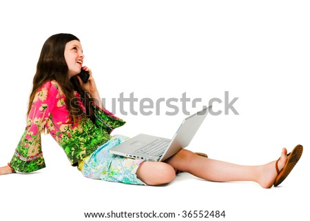 Smiling girl using a laptop and a mobile isolated over white - stock photo