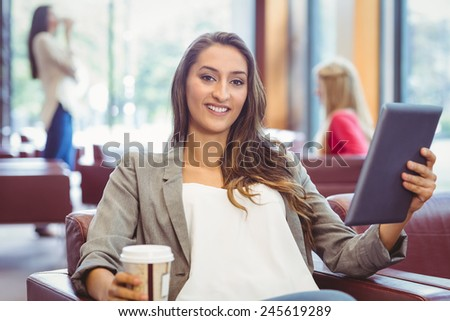 Smiling girl using digital tablet and holding disposable cup in library