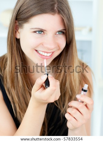 Smiling girl using lipstick at home - stock photo