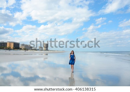 Smiling girl walking on beautiful beach, hotels, buildings in the background, reflection of beautiful sky and clouds in the water on the beach, Jacksonville, Florida. - stock photo
