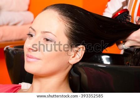 Smiling girl washing hair in hairdressing salon. - stock photo