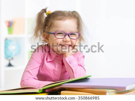 Smiling girl wearing spectacles reading book