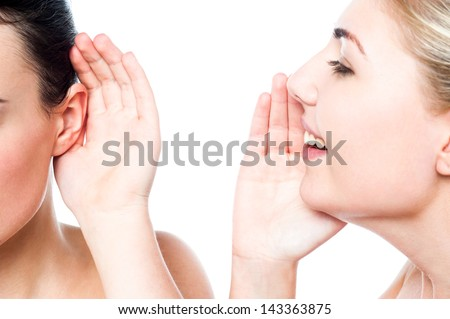 Smiling girl whispering into her friends ear. - stock photo