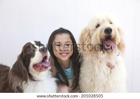 smiling girl who is sandwiched between two dogs