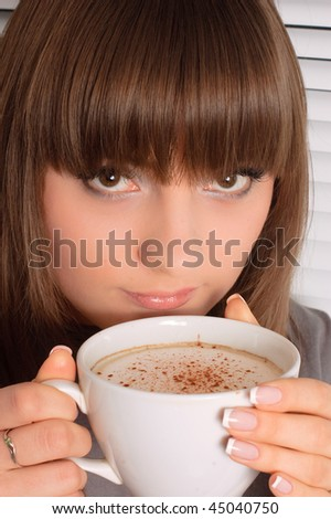 Smiling girl with a cup of cappuccino - stock photo