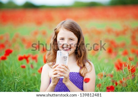 Smiling girl with a large glass of cold sparkling mineral water clasped in her hands a she quenches her thirst in a colourful red poppy field - stock photo