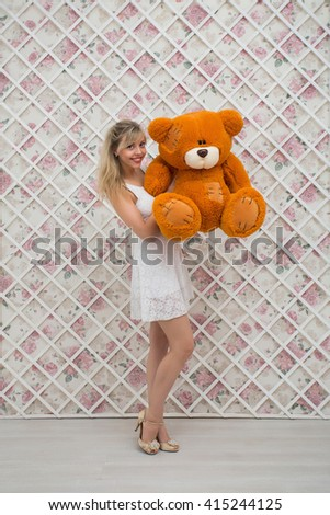 Smiling girl with a teddy bear on a background with flowers - stock photo