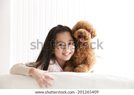 Smiling girl with a toy poodle