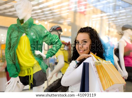 smiling girl with bags stand near mannequin - stock photo