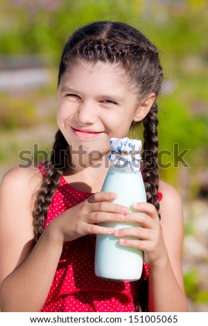 Smiling girl with bottle of milk - stock photo
