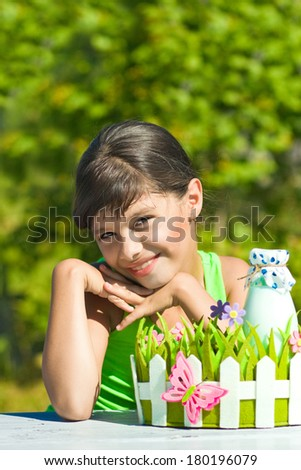 Smiling girl with bottle of milk  in decorative basket with flowers  - stock photo