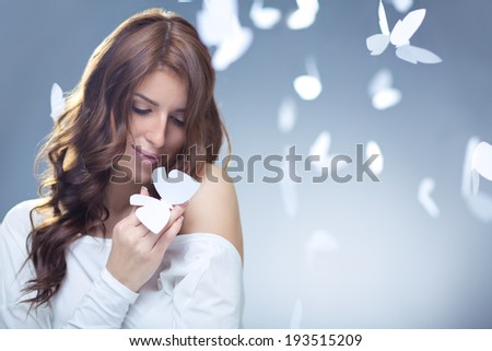Smiling girl with butterflies in studio - stock photo