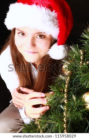 smiling girl with christmas tree over dark background - stock photo