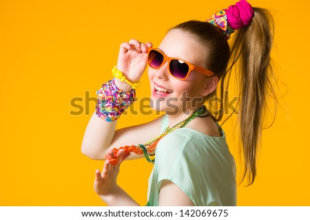 Smiling girl with colorful clothes wearing sunglasses, yellow background