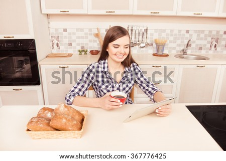 Smiling girl with cup of tea reading news on tablet in kitchen - stock photo