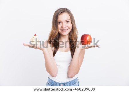 Smiling girl with cupcake and large red apple. She is wearing blue jeans and white tank top. Concept of right food choice
