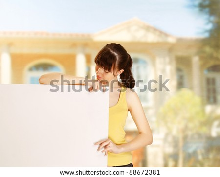 Smiling girl with empty billboard outdoors - stock photo