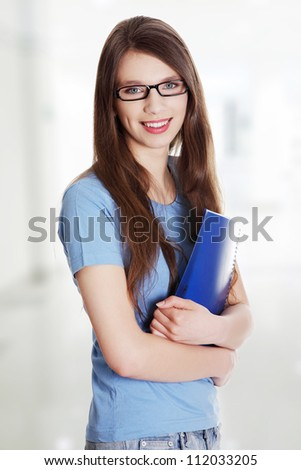 Smiling girl with folder. Long hair and black glasses. - stock photo