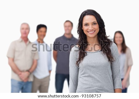 Smiling girl with friends standing behind her against a white background - stock photo