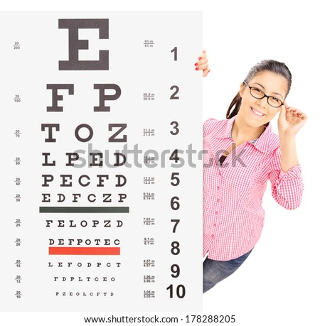 Smiling girl with glasses standing behind eyesight test, isolated on white background, shot with tilt and shift - stock photo