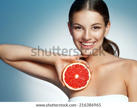 Smiling girl with grapefruit cut in half fruit in hand / photoset of attractive girl holding a cut piece of Sicilian orange on blue background  - stock photo