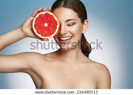 Smiling girl with grapefruit, natural organic raw fresh food concept / photoset of attractive girl holding a cut piece of Sicilian orange on blue background  - stock photo