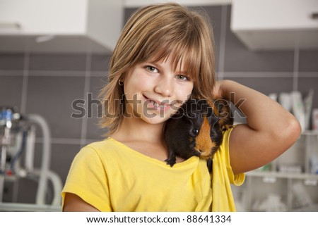 smiling girl with guinea pig on her shoulder standing in a veterinarian practice - stock photo