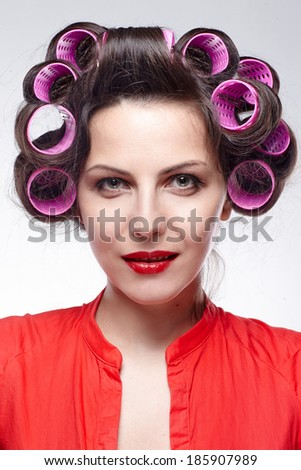 Smiling girl with hair rollers - stock photo
