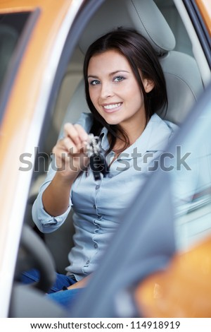 Smiling girl with keys in a car - stock photo