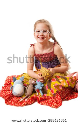 smiling girl with knitted homemade toys sitting on the floor