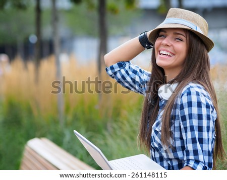 Smiling girl with laptop outdoors