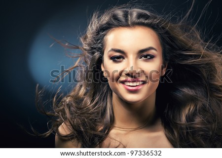 smiling girl with long hair on wind - stock photo