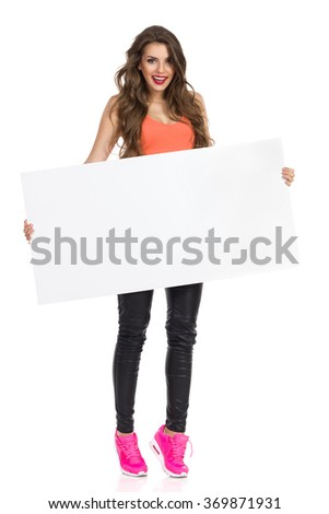 Smiling girl with long hair orange shirt and pink sneakers standing tiptoe, holding blank placard and looking at camera. Full length studio shot isolated on white. - stock photo