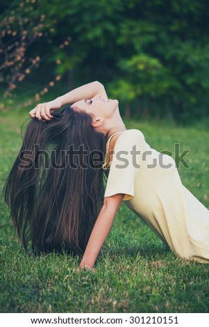 smiling girl with long healthy hair enjoy in nature, profile, sit in grass with hand in hair - stock photo