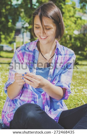 Smiling Girl with mobile phone in park