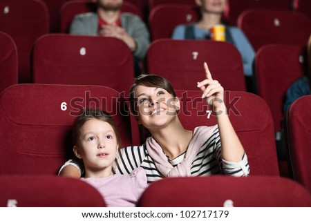 Smiling girl with mother at the cinema - stock photo