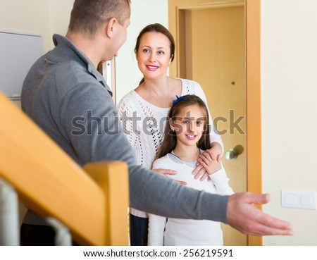Smiling girl with mother visiting middle aged man indoors - stock photo