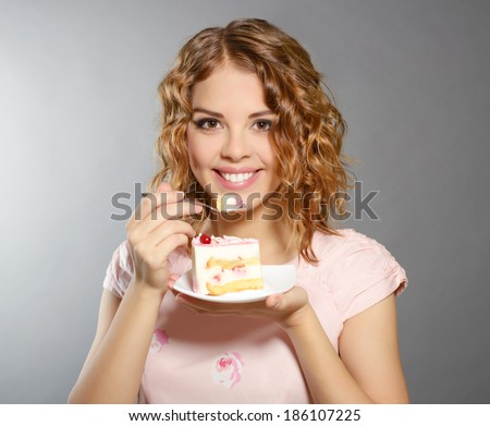 Smiling girl with piece of cake on light background - stock photo