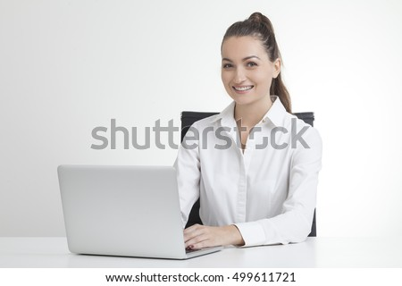 Smiling girl with ponytail is sitting at her laptop in perfectly white office. Concept of HR work. Mock up