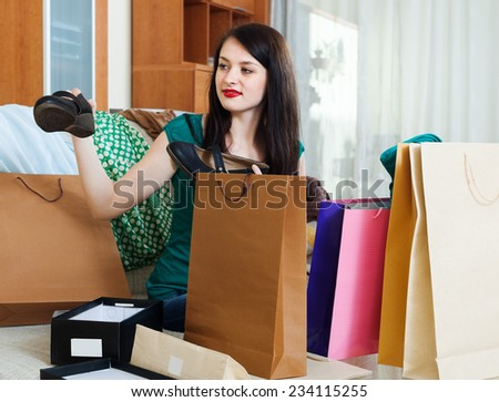 Smiling girl with  purchases at her home